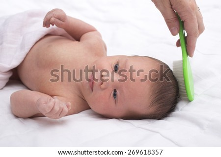 Newborn baby boy with mother combing