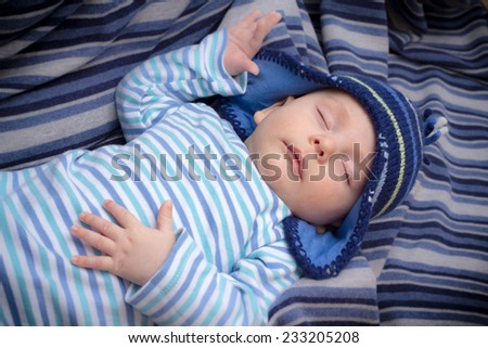 Newborn baby boy with striped hat and pajama sleeping on a blue blanket