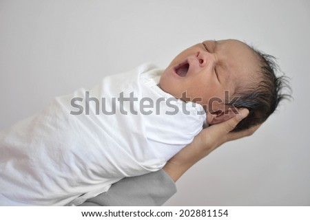 Newborn baby boy yawning held in mom's hands - stock photo