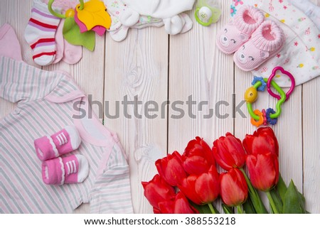 newborn baby clothes on wooden background - stock photo