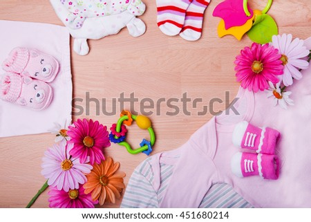 newborn baby clothes with toys on wooden background   - stock photo