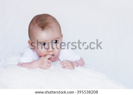 Newborn Baby Curiously Observing Environment on a Soft Blanket and Finger in Mouth - stock photo