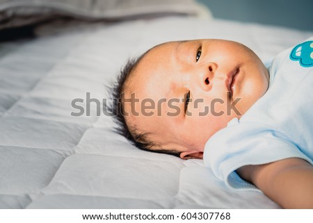 Newborn baby cute sleeping on blanket at home.