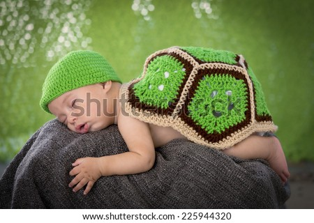 Newborn Baby Dressed Like a Turtle on a Rock Happy Halloween Greeting Card Green Background - stock photo