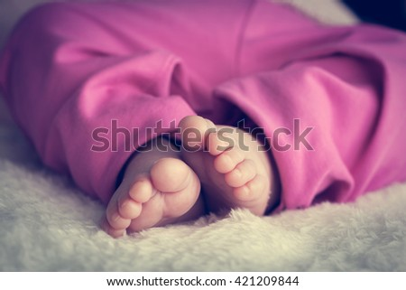 Newborn baby feet close-up on white fur. Concept of childhood, infant, innocence. Vintage style - stock photo