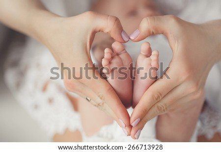 Newborn baby feet in mother hands.Masseur massaging little baby's foot, shallow focus. Newborn baby feet in mother's hands.Mother making massage of child's foot - stock photo