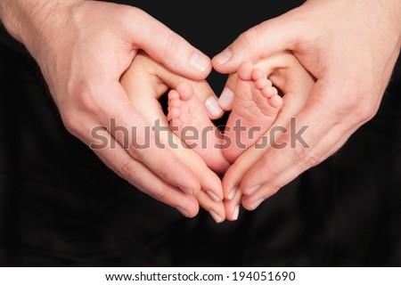 Newborn baby feet in parents hands - stock photo