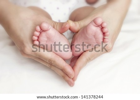 Newborn baby feet in the mother hands - stock photo