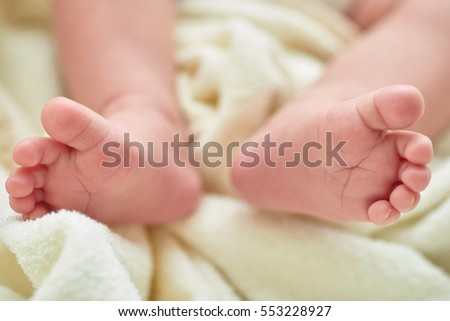 Newborn baby feet on a white towel