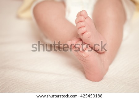 Newborn baby feet on bed in vintage color filter - stock photo