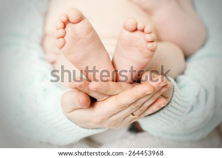 Newborn baby feet on female hands, close-up - stock photo