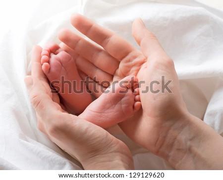 Newborn baby feet on mothers hands - stock photo