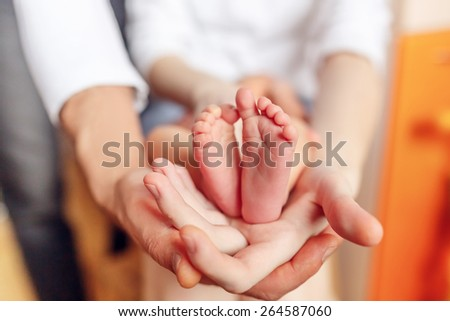 Newborn baby feet on parents hands - stock photo