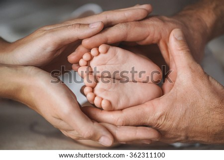 Newborn baby feet parents holding in hands.Mom and Dad hold baby legs. Taking care of a newborn.Children's feet in hands of mother and father. Feet of the tiny Newborn Child. Parents and Child.
