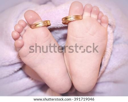 Newborn Baby Feet Gold Wedding Rings Stock