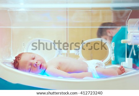 newborn baby get the light therapy in infant incubator - stock photo