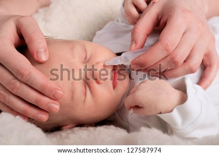 Newborn baby gets nose drops - stock photo