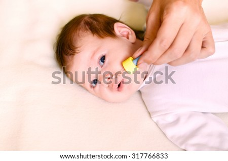 newborn baby gets nose drops