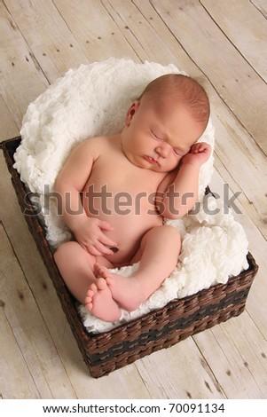 Newborn baby girl, asleep in a basket. - stock photo