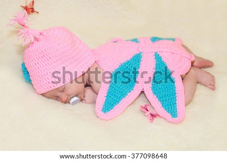 Newborn baby girl, asleep on a blanket in a suit of a butterfly.Close-up beautiful sleeping baby girl.  A portrait of a beautiful, newborn baby girl wearing a large,fabric rose headband. Closeup photo - stock photo