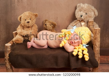 Newborn baby girl dressed as Goldilocks and sleeping on a rustic wooden bed surrounded by 3 plush toy bears. - stock photo