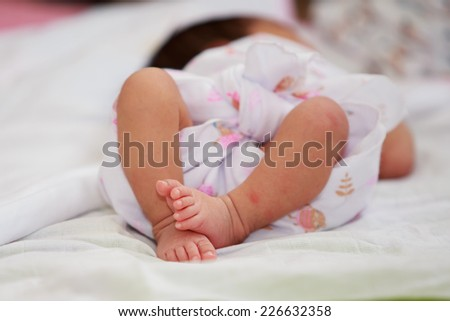 Newborn baby girl feet. A closeup with a candid appeal. The baby skin is caucasian tone. - stock photo