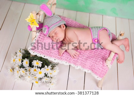 Newborn baby girl in a knitted hare costume sleeping on a wooden crib birch - stock photo