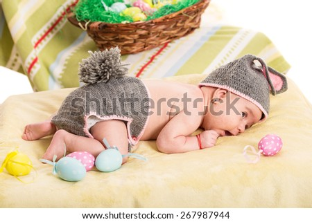 Newborn baby girl in crochet bunny costume  with Easter eggs - stock photo