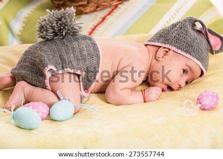 Newborn baby girl in crochet bunny costume with Easter eggs