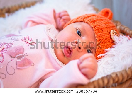 Newborn baby girl in orange knitted hat