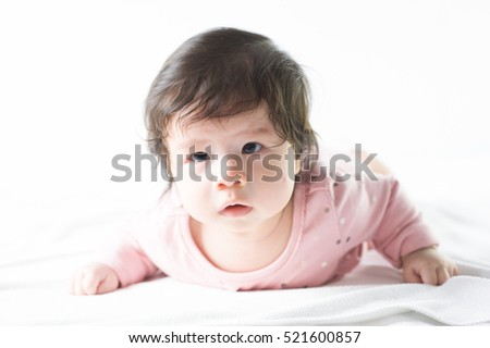 newborn baby girl in pink dress on white background