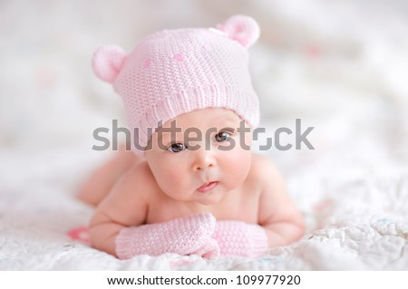newborn baby girl in pink knitted bear hat - stock photo