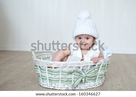 newborn baby girl in white knitted pompon hat lies at basket
