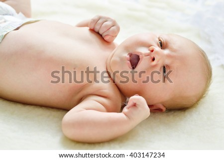 newborn baby girl lying down and yawning