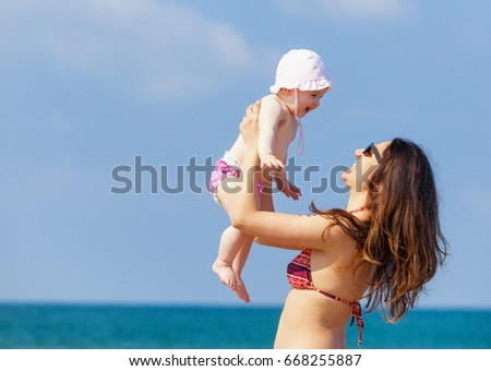 Newborn baby girl playing with mom at the beach.