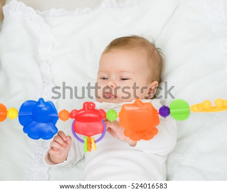 Newborn baby girl playing with toy rattle lying on back