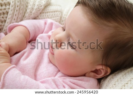 Newborn baby girl posed in a bowl on her back, on knit blanket, smiling looking at camera
