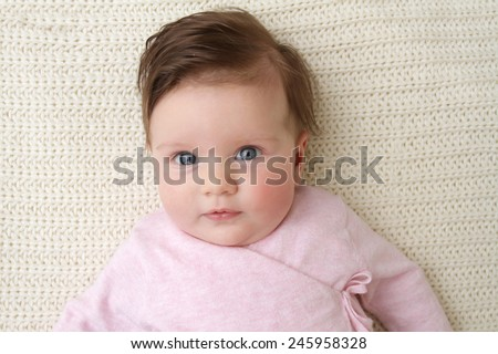 Newborn baby girl posed in a bowl on her back, on knit blanket, smiling looking at camera - stock photo