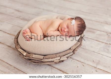 Newborn baby girl posing in basket