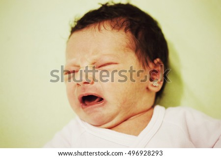 Newborn baby girl shouting , face closeup