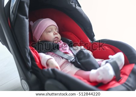 Newborn baby girl sitting in a car seat with safety belt buckled up.