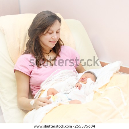 Newborn baby girl sleeping. Her mother looking at. - stock photo