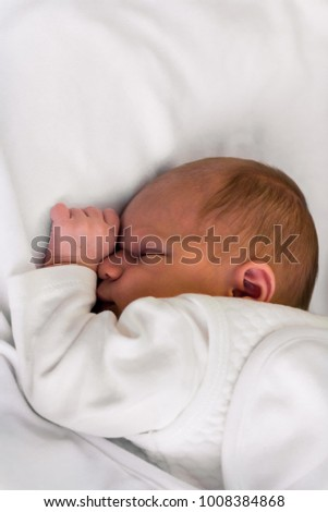 Newborn baby girl sleeping in white clothes, blanket and sheet.