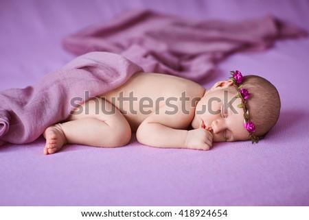 Newborn baby girl sleeping on pink background. - stock photo