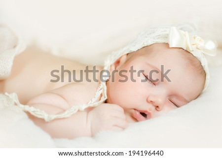 Newborn baby girl sleeping on the bed
