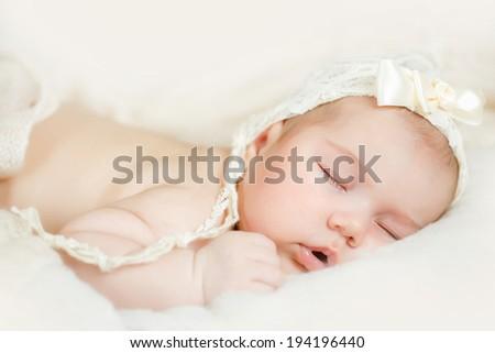 Newborn baby girl sleeping on the bed - stock photo