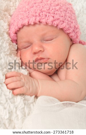 Newborn baby girl wearing a pink knitted hat. - stock photo