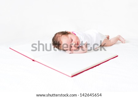Newborn baby girl with a huge book - stock photo