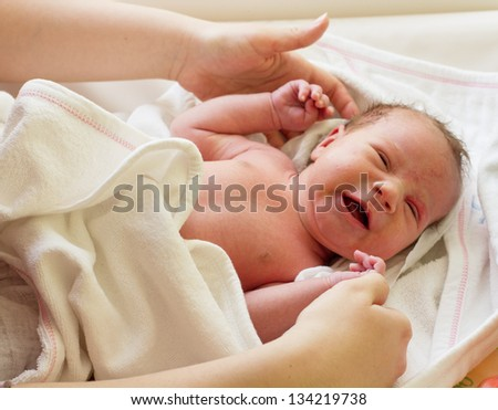 Newborn baby girl with colic problem crying.