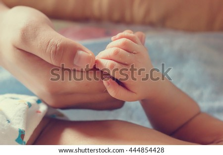 Newborn baby hand holding mother hand in vintage tone style : mother day, holiday concept - stock photo